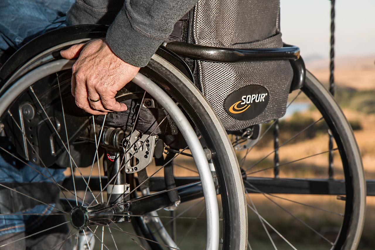 picture of an old man with a wheelchair wheeling his way towards prescription assistance programs