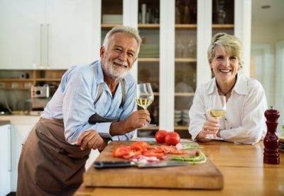 two senior citizens enjoying wine and cooking dinner at the kitchen island