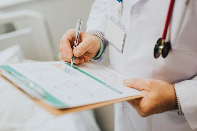 doctor writing a script on clipboard