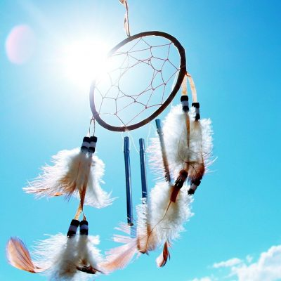 dreamcatcher hanging outside with bright blue sky