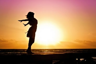 woman feeling free on a dock on ocean during sunrise