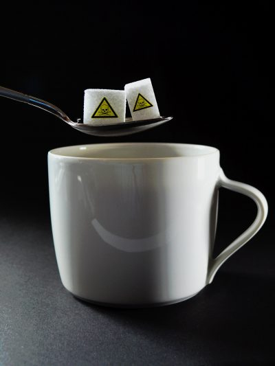 Two sugar cubes with poison hazard stickers, held on a spoon over coffee mug