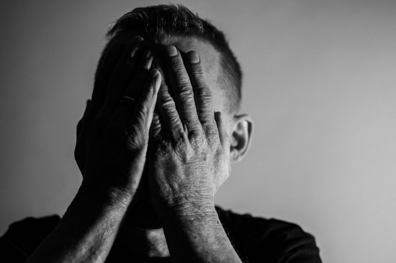 man holding face in hands fatigue depression