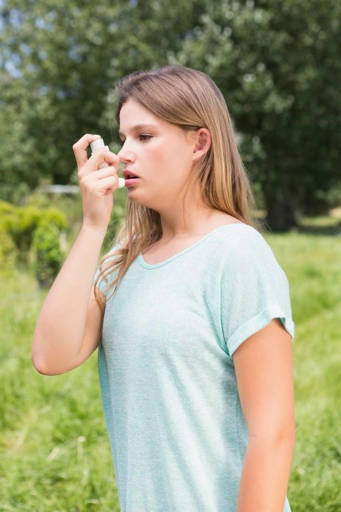 Woman taking Spiriva through inhaler